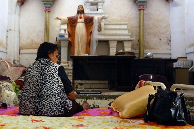 An Iraqi Christian woman, fleeing the violence in the city of Mosul, sits inside the Sacred Heart of Jesus Chaldean Church in Telkaif.