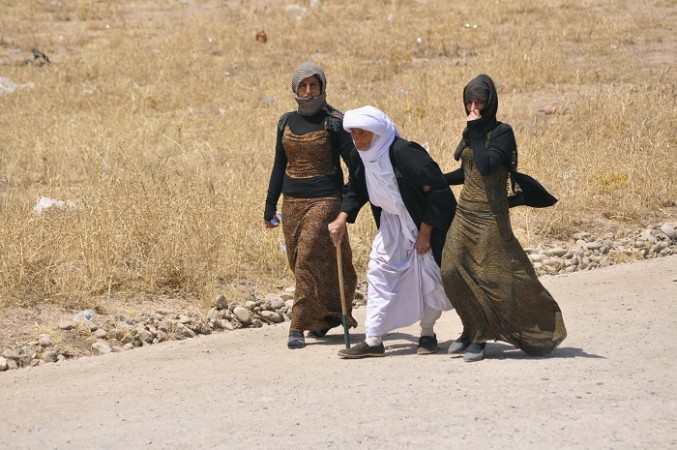 Displaced families from the minority Yazidi sect, fleeing the violence, walk on the outskirts of Sinjar, west of Mosul, 5 August.