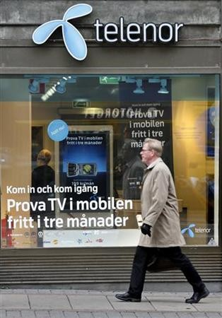 A pedestrian walks past a Telenor store in central Stockholm