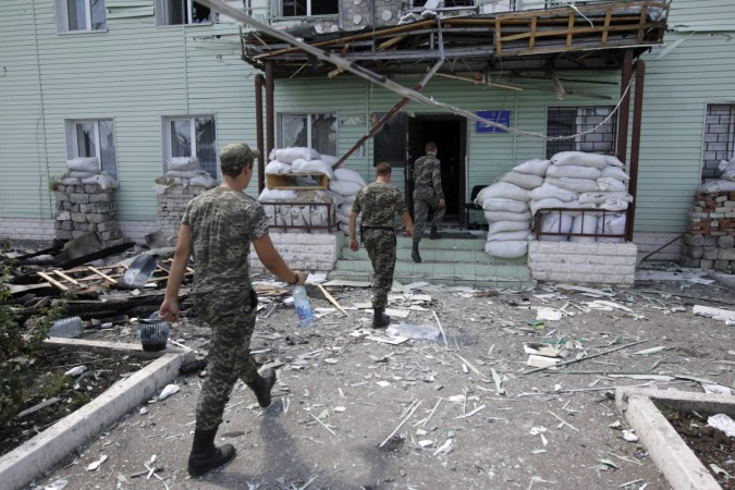 Ukrainian border guards walk into the headquarters of a local Ukrainian frontier guard detached unit, which according to Ukrainian servicemen, was attacked by weapons fired from the territory of Russia, in the town of Milove, in the Luhansk region August
