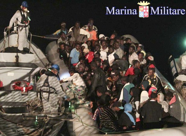 Migrants sit in their boat during a rescue operation by Italian navy ship Scirocco about 40 nautical miles off the coast of Libya in this handout picture released on June 14, 2014 by the Italian Marina Militare.