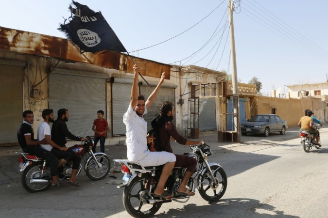 A resident of Tabqa city touring the streets on a motorcycle waves an Islamist flag in celebration after Islamic State militants took over Tabqa air base, in nearby Raqqa city August 24, 2014. I
