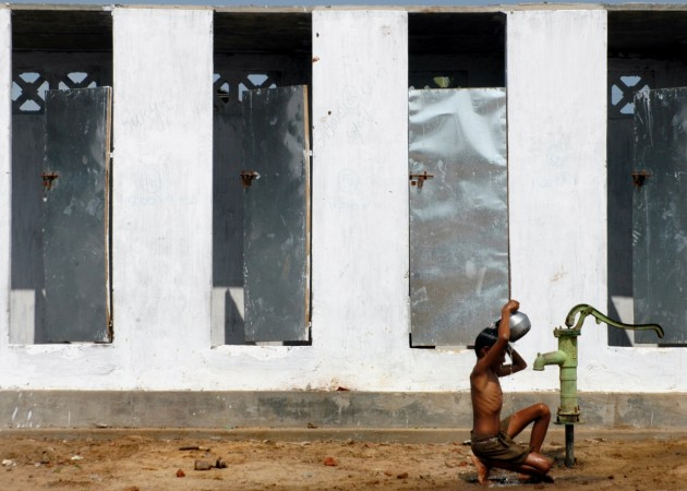 A boy takes bath outside newly built toilets in a village