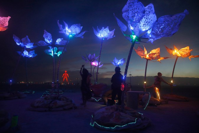 Festival-goers move around the art installation Pulse & Bloom after it is illuminated as night falls in the Black Rock Desert of Nevada.