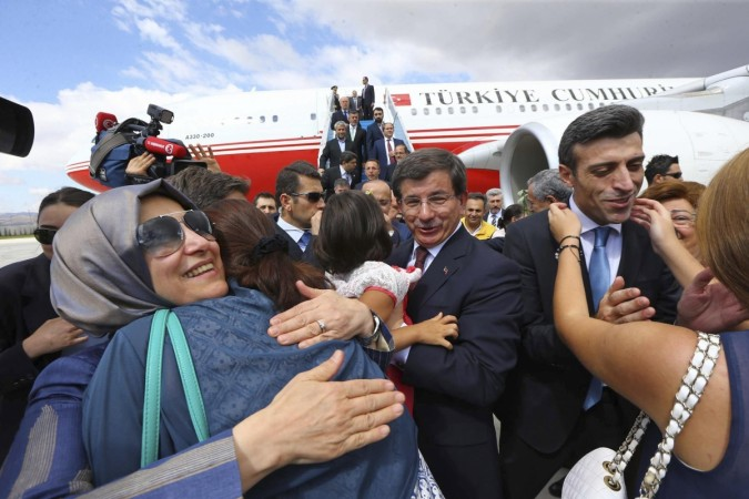Turkish Consul General of Mosul Yilmaz is welcomed by his relatives as Turkish Prime Hakan Goktepe looks on.
