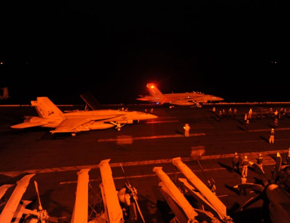 An F/A-18E Super Hornet, attached to Strike Fighter Squadron (VFA) 31, and an F/A-18F Super Hornet, attached to Strike Fighter Squadron (VFA) 213, prepare to launch from the flight deck of the aircraft carrier USS George H.W. Bush (CVN 77) to conduct stri