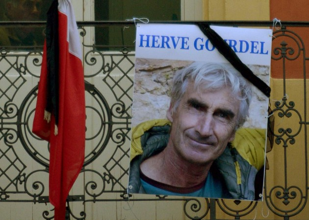 A portrait of mountain guide of Frenchman Herve Gourdel hangs near a French flag outside the town hall in Saint-Martin-Vesubie, September 24, 2014. Algerian militants have released a video that appears to show them beheading Gourdel who was kidnapped on S