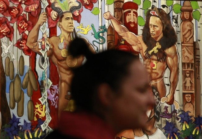 A visitor passes by a painting, displaying Russian Prime Minister Vladimir Putin (R) and U.S. President Barack Obama