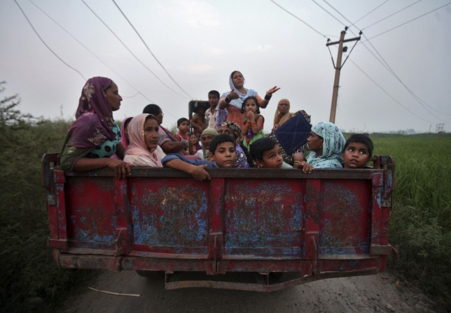 Indian villagers sit in a tractor trolley as they move to safer places at Devi Garh village near Jammu, October 7, 2014. REUTERS/Mukesh Gupta