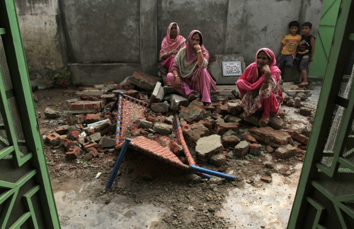 Villagers sit on the debris of their house.