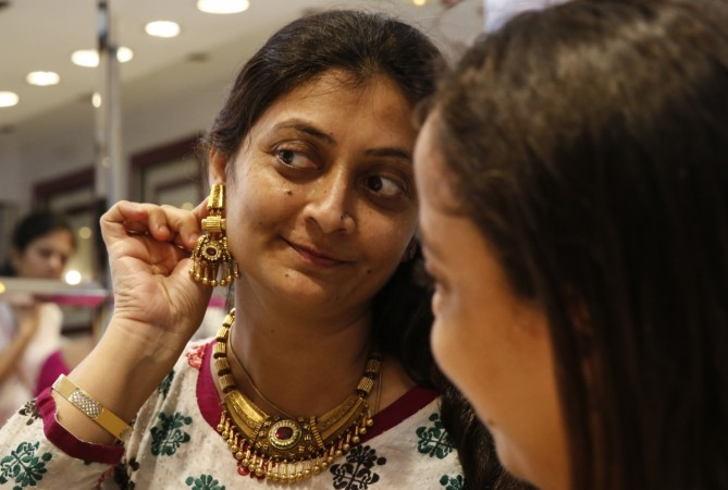 A woman tries on a gold earring inside a jewellery showroom at a market in Mumbai