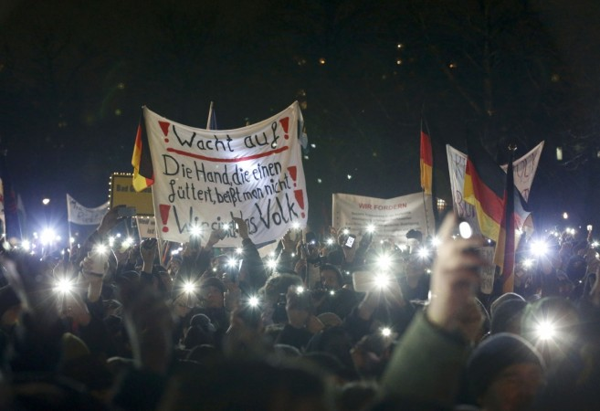 Participants use lights on their portable phones as they take part in a demonstration called by anti-immigration group PEGIDA, a German abbreviation for