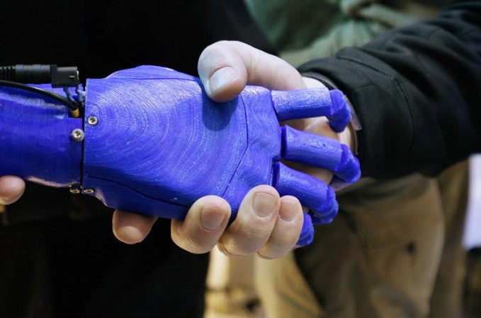 A man shakes hands with a robotic prosthetic hand in the Intel booth at the International Consumer Electronics show