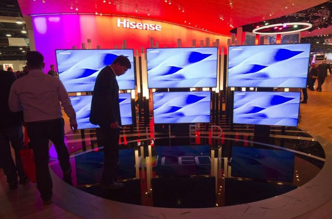 A man looks over a display of Hisense 4K televisions during the 2015 International Consumer Electronics Show