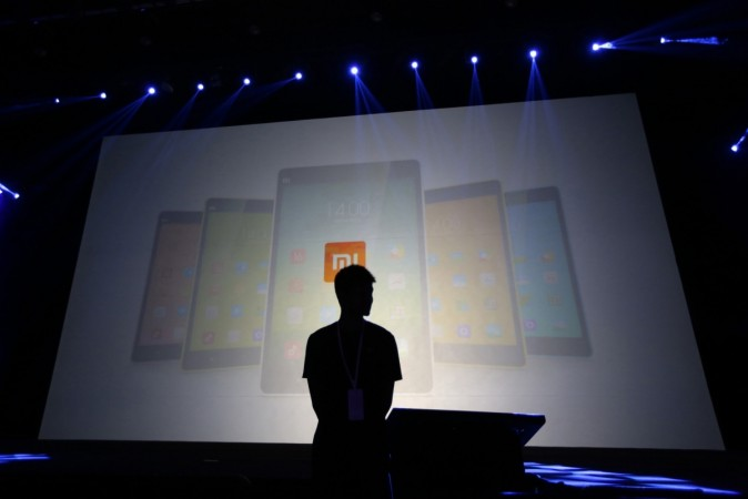 A security guard stands in front of a screen showing Xiaomi mobile phones