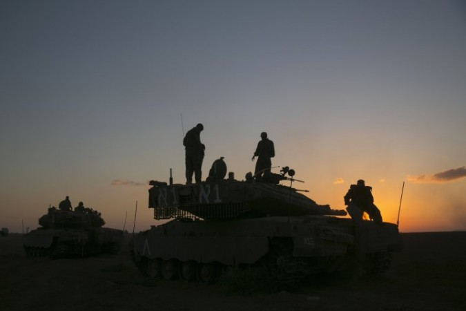 Israeli soldiers stand on top of a tank near Gaza