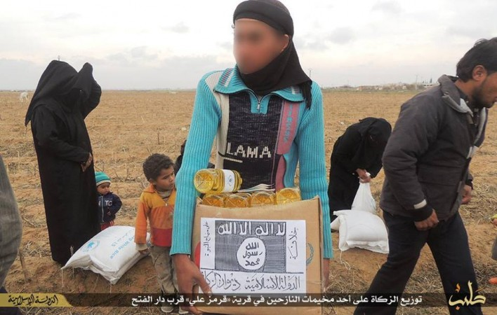 A Syria refugee carries a cardboard box containing food parcel distributed by ISIS. The images shows that the Islamic State has pasted its logo over the WFP label.
