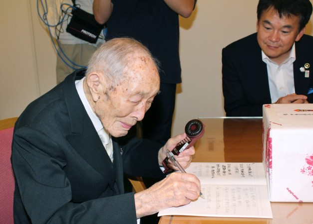 Sakari Momoi (L), a resident of Saitama prefecture, writes a message to communicate with Saitama Mayor Hayato Shimizu (R) in Tokyo, in this Kyodo file photo taken September 2013.