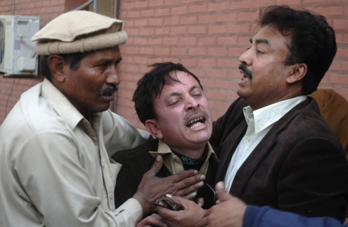 A man cries over the death of his relative, who was killed in an explosion in a Shi'ite mosque, outside a hospital in Peshawar February 13, 2015.