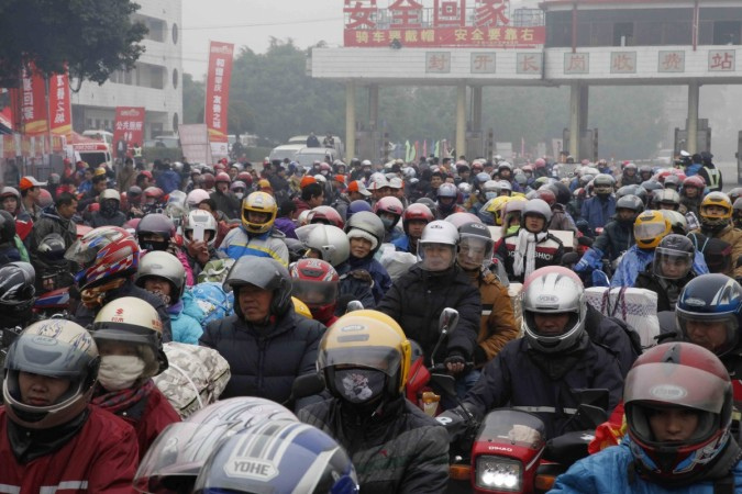 Migrant workers ride their motorcycles with families and friends, as they past a checkpoint on their way home for the upcoming Spring Festival, on a hazy day in Fengkai county, Guangdong province, February 12, 2015