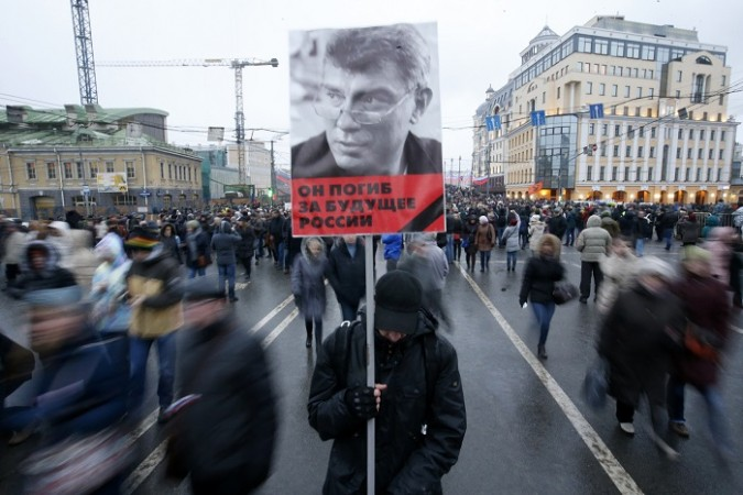 A man holds a poster of Kremlin critic Boris Nemtsov, who was shot dead on Friday night, during a march to commemorate him in central Moscow March 1, 2015.