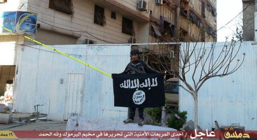 An Isis fighters poses with the black flag of the Sunni militant group inside Yarmouk camp.