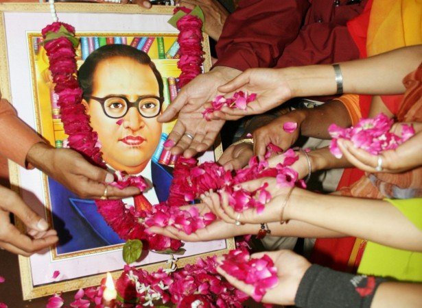 People scatter rose petals in front of a portrait of Dr BR Ambedkar