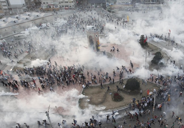 Protesters run as riot police fire teargas during a protest at Taksim Square in Istanbul June 11, 2013