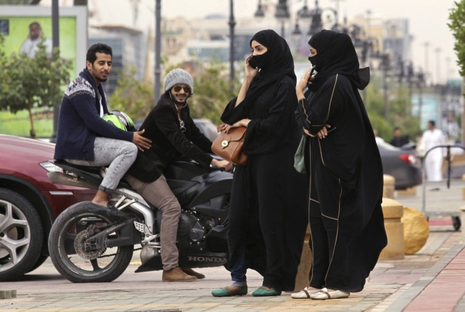 A woman speaks on the phone as men ride a motorcycle on a cloudy day in Riyadh november 17, 2013.