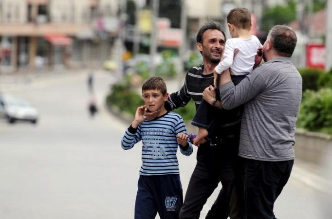A man reunites with his family members after they were rescued by the police near a police checkpoint in Kumanovo, Macedonia May 9, 2015.