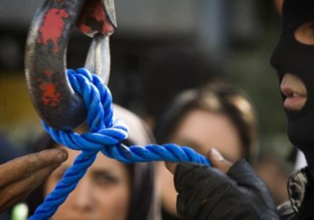 An Iranian executioner checks the rope before a public hanging.