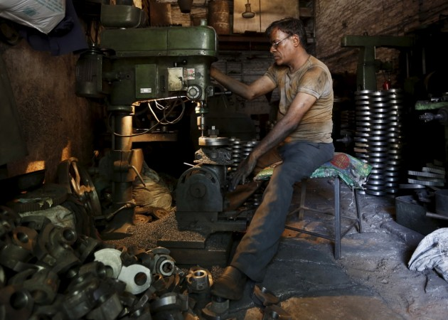 A worker operates a drilling machine as he makes parts for diesel water pumps inside his workshop in Ahmedabad, India, May 4, 2015.
