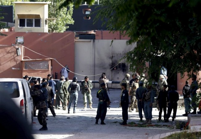 Afghan security force and Nato troops stand at the gate of a guesthouse after an attack in Kabul, Afghanistan