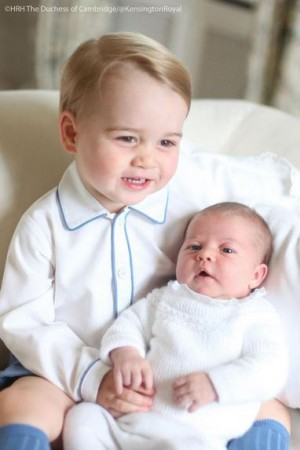 Prince George smiles while holding little sister Princess Charlotte