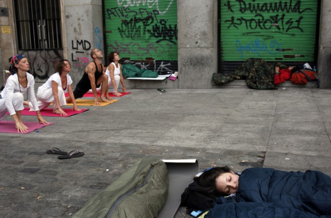 Demonstrators sleep as people practice yoga at Madrid's Puerta del Sol.