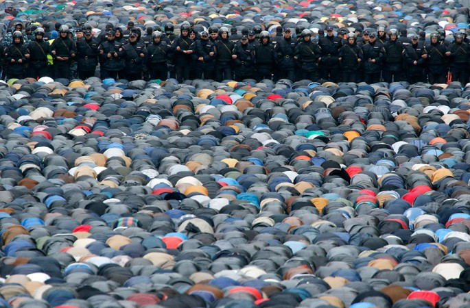 Russian interior ministry members stand guard as Muslims attend an Eid Al-Adha mass prayer in Moscow