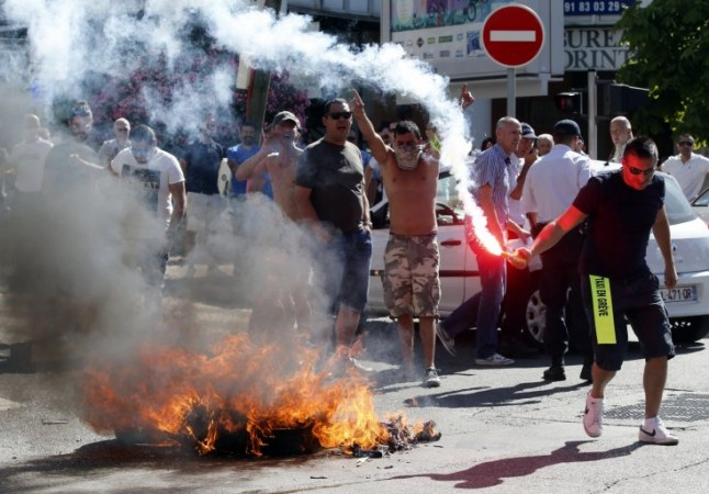Taxi drivers on strike burn tyres during a national protest against car-sharing service Uber in Marseille, France