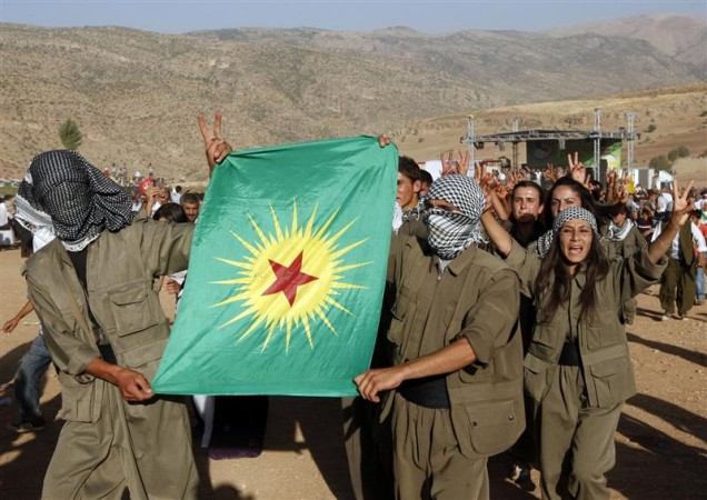 Turkish Kurdish youths dressed as PKK militants chant slogans in the town of Eruh, southeastern Turkey, in this August 15, 2009 file photo