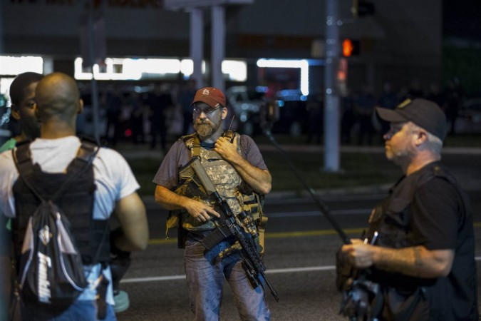 Members of the Oath Keepers walk with their personal weapons on the street during protests in Ferguson, Missouri, on Tuesday.