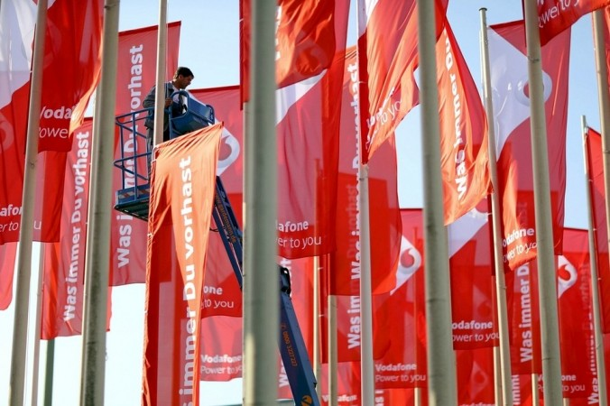 A worker installs advertising flags of British telecommunications company Vodafone outside an event