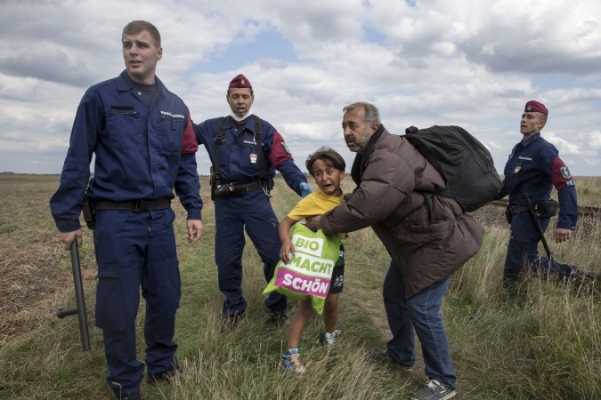 A migrant carrying a child falls after tripping on a TV camerawoman (R) while trying to escape from a collection point in Roszke village, Hungary, September 8, 2015.