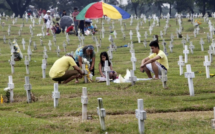 People visit a grave Thursday, the eve of All Saints' Day, at a cemetery in Manila, Philippines.