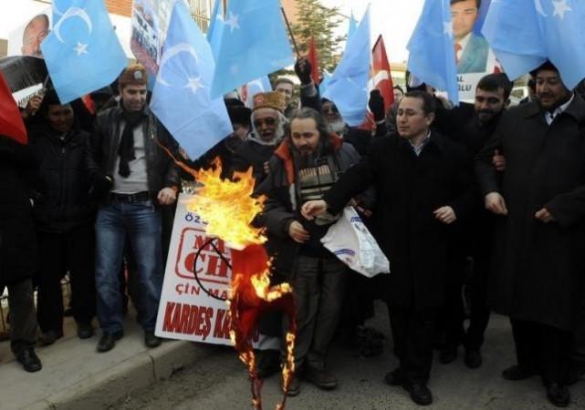 Ethnic Uighur demonstrators, waving blue East Turkestan flags, set fire to a Chinese flag