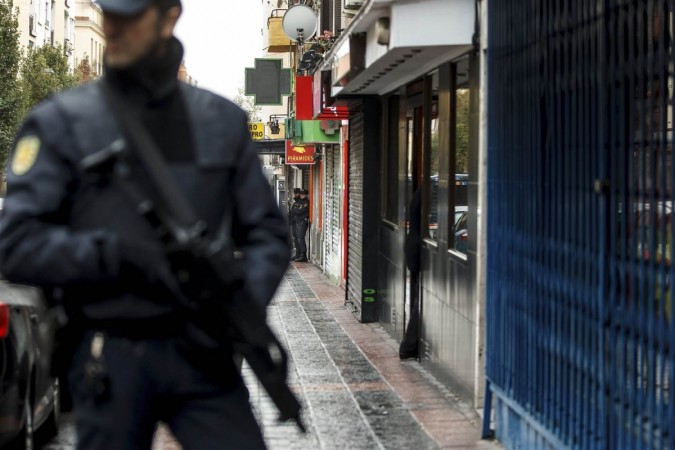 Police guard the home of a man suspected to be a member of a group linked to ISIS in Madrid