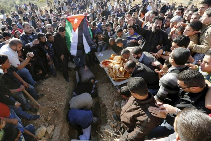 Fadi (C), brother of Anwar Abu Zeid, the Jordanian officer whom the government said killed five people, holds Jordanian national flags during his brother's funeral in Raymun village in the city of Jerash, north of Amman, Jordan, November 12, 2015. REUTERS