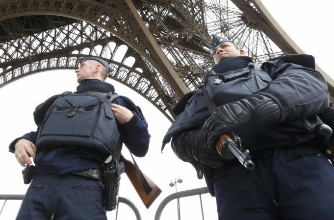 Police take up position under the Eiffel Tower the morning after a series of deadly attacks