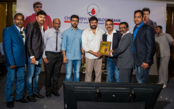 Chiranjeevi and Ram Charan giving mementos to fans