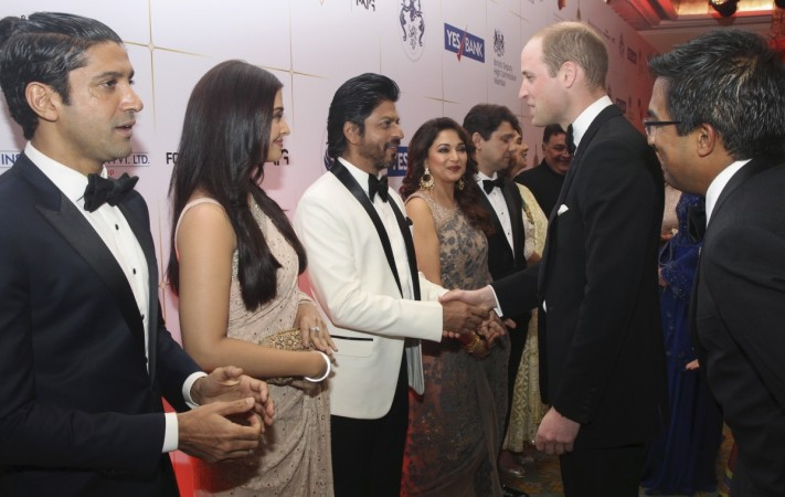 ritain's Prince William shakes hands with Bollywood actor Shah Rukh Khan at reception