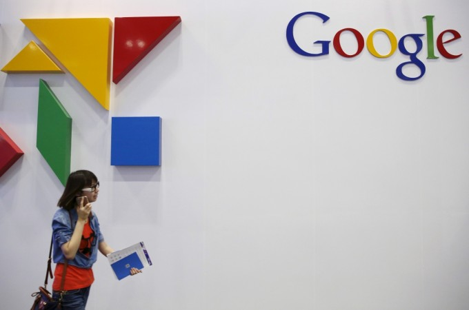 A woman walks past a logo of Google at the GMIC event in Beijing