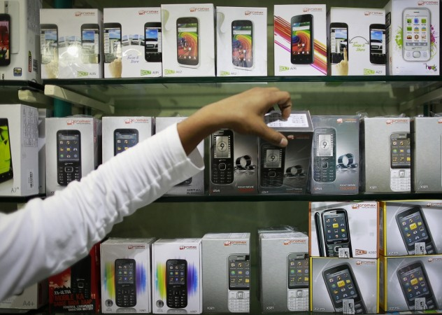 Employee takes out a Micromax mobile phone from the display at a mobile store